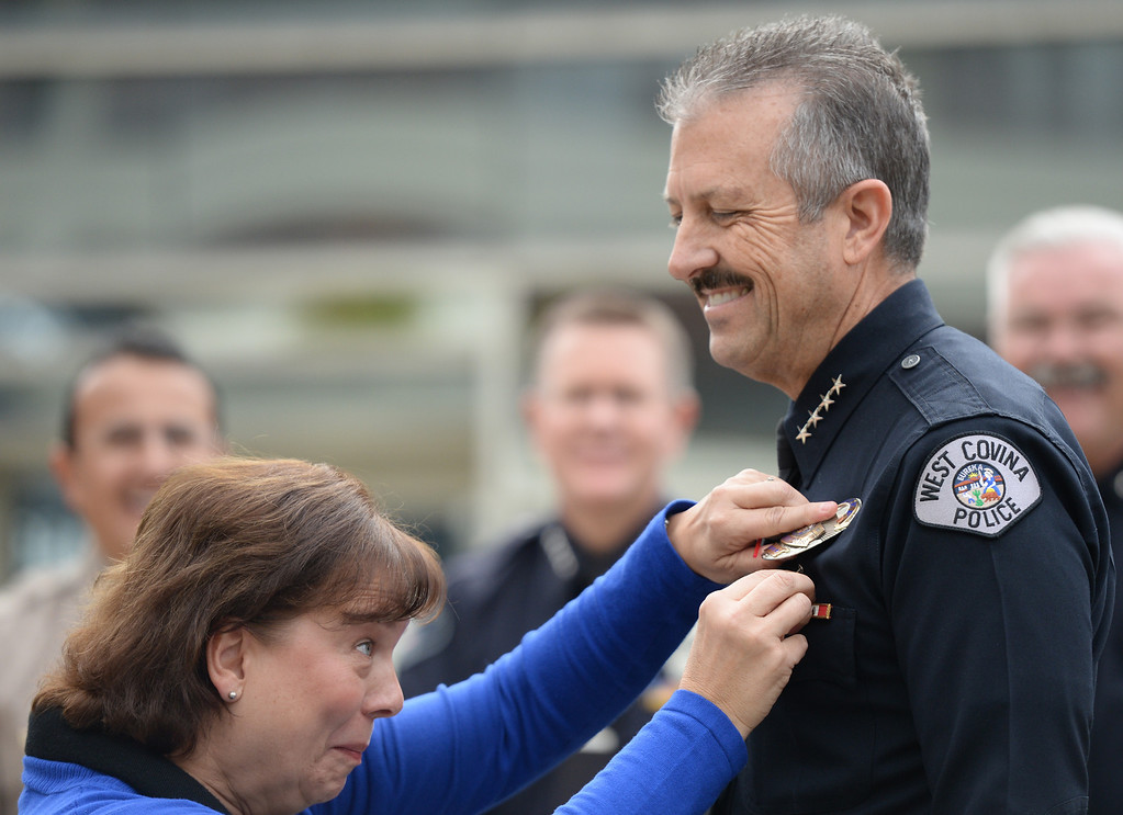 Description of . William Faulkner gets his badge pinned on by his wife, Lori, after he is sworn in as the new Police Chief during a ceremony at the West Covina Civic Center on Thursday February 6, 2014. Faulkner comes with 30 years of experience after spending much of his career at the Fontana Police Department. (Staff Photo by Keith Durflinger/San Gabriel Valley Tribune)