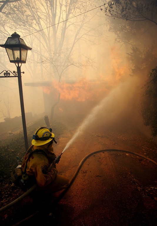 Description of . Ten years ago this month the arson caused Old Fire, fanned by Santa Ana winds burned thousands of acres, destroyed hundreds of homes and caused six deaths. The fire burned homes in San Bernardino, Highland, Cedar Glen, Crestline, Running Springs and Lake Arrowhead and forced the evacuation of thousand of residents. A firefighter kneels down while spraying water on a house fire near Crestline, on Sunday October 26, 2003 on the second day of the Old Fire. (Staff file photo/The Sun)