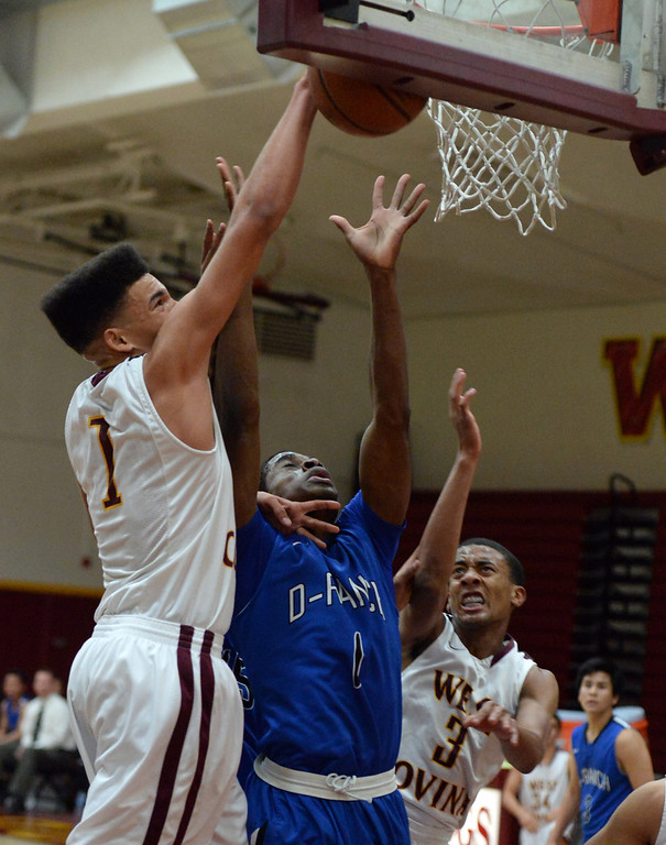 Description of . West Covina's Michael Fallon (1) rebounds over Diamond Ranch's Ernest Ugoagu (1) in the first half of a prep basketball game at West Covina High School in West Covina, Calif., on Wednesday, Jan. 8, 2014. (Keith Birmingham Pasadena Star-News)