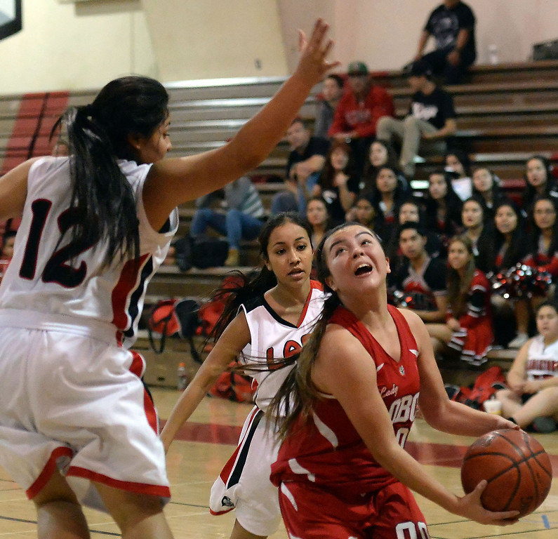Description of . Workman's Alicia Aguirre (00) drives to the basket past Gladstone's Erika Sanchez (12) in the first half of a prep basketball game at Gladstone High School in Covina, Calif., on Friday, Jan. 17, 2014. (Keith Birmingham Pasadena Star-News)
