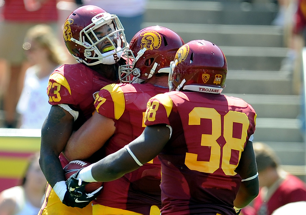 Description of . Southern California running back Tre Madden (23) reacts with teammate offensive tackle Kevin Graf (77) and fullback Jahleel Pinner (38) after catching a 5 yard touchdown pass against Boston College during the first half of an NCAA college football game in the Los Angeles Memorial Coliseum in Los Angeles, on Saturday, Sept. 14, 2013.