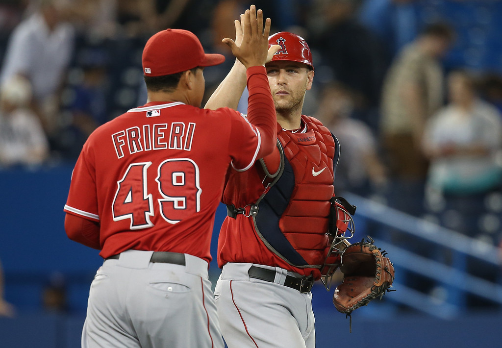 Description of . TORONTO, CANADA - SEPTEMBER 11: Chris Iannetta #17 of the Los Angeles Angels of Anaheim celebrates their victory with Ernesto Frieri #49 during MLB game action against the Toronto Blue Jays on September 11, 2013 at Rogers Centre in Toronto, Ontario, Canada. (Photo by Tom Szczerbowski/Getty Images)