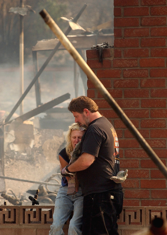 Description of . Ten years ago this month the arson caused Old Fire, fanned by Santa Ana winds burned thousands of acres, destroyed hundreds of homes and caused six deaths. The fire burned homes in San Bernardino, Highland, Cedar Glen, Crestline, Running Springs and Lake Arrowhead and forced the evacuation of thousand of residents. Sam Goldstein hugs his wife Tami Goldstein after Tami is overcome while searching through the remains of their home at 1436 E. Ralston Avenue, in San Bernardino. The Goldstein's home was destroyed by the Old Fire. (Staff file photo/The Sun)