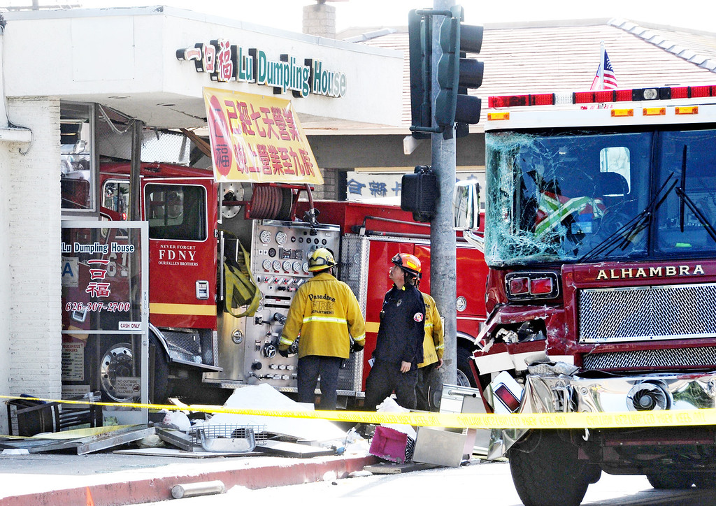 Description of . Emergency personnel investigate the scene where a fire crashed into Lu Dumpling House restaurant after it two fire engines, one from Monterey Park and Alhambra Fire collided with  at the intersection of Emerson Avenue and Garfield Avenue in Monterey Park on Wednesday, April 16, 2014. (Photo by Walt Mancini/ Pasadena Star-News)