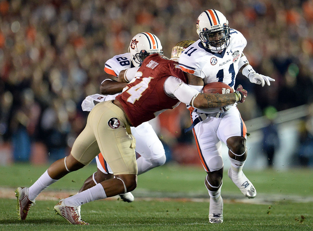Description of . Auburn tight end Brandon Fulse (11) runs for yardage past Florida State linebacker Terrance Smith (24) in the first half of the BCS National Championship game at the Rose Bowl in Pasadena, Calif., on Monday, Jan. 6, 2014.   (Keith Birmingham Pasadena Star-News)