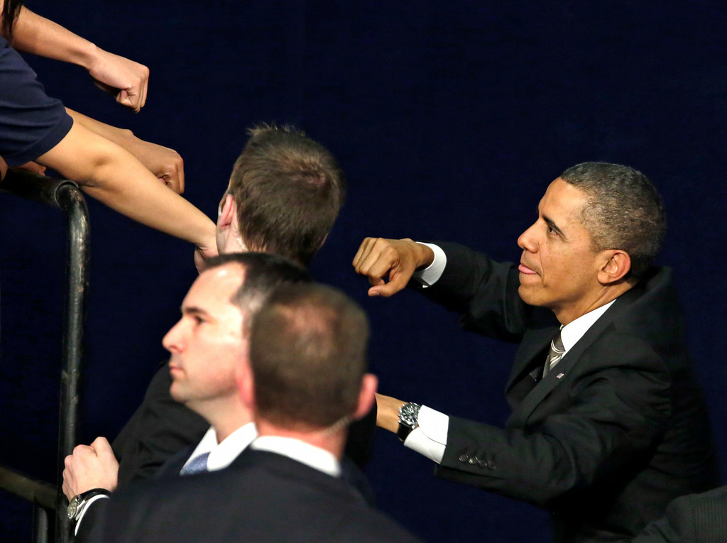 Description of . President Barack Obama acknowledges the crowd as he exchanges fist bumps with the audience after speaking at Hyde Park Academy, Thursday, Feb. 14, 2013, in Chicago. (AP Photo/M. Spencer Green)