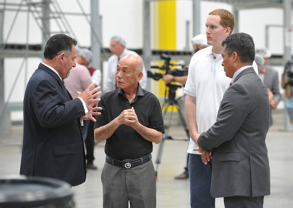 Description of . Irwindale Mayor Mark Breceda, left, and City Councilman Julian Miranda , right, tour the Huy Fong Foods plant with CEO David Tran on Tuesday May 27, 2014. A team from Governor Jerry Brown's Office of Business and Economic Development joins the tour of the 650,000 square-foot facility that the council voted has created a public nuisance. (Photo by Keith Durflinger/Whittier Daily News)