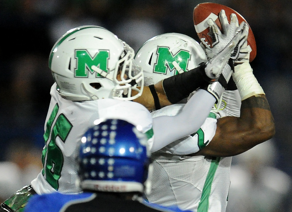 Description of . Monrovia's Kurt Scoby (2) catches a pass over teammate Jordan Nathan (16) and runs for a touchdown against San Marino in the first half of a prep football game at Monrovia High School in Monrovia, Calif., on Friday, Nov. 8, 2013. 