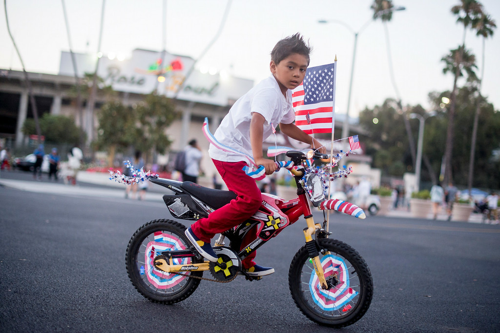 Description of . Daniel Gomez, 6, of Whittier, rides around the Rose Bowl with his decorated bike during the 88th Annual Fourth of July Celebration, Americafest at the Rose Bowl in Pasadena Friday night, July 4, 2014. (Photo by Sarah Reingewirtz/Pasadena Star-News)