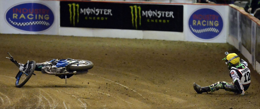 Description of . Patryk Dudek (12) wrecks in the third race during the Monster Energy Speedway Cycles at the Industry Speedway in the Industry Hills Grand Arena in Industry, Calif., on Saturday, Dec. 28, 2013.     (Keith Birmingham Pasadena Star-News)
