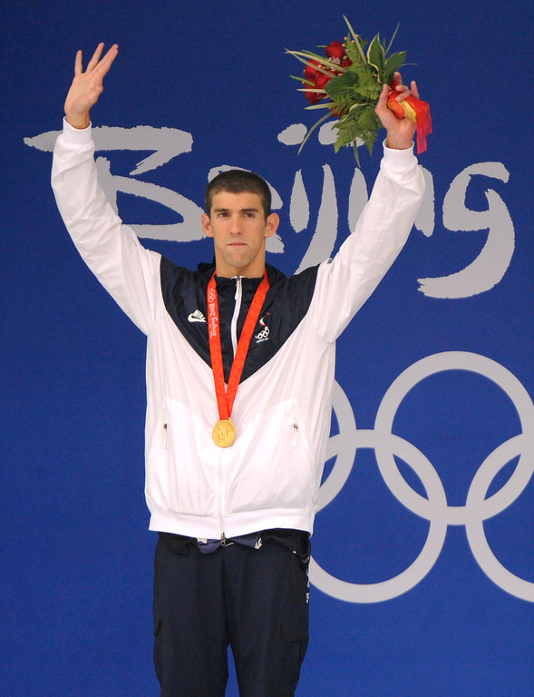 Description of . Gold medalist Michael Phelps of the United States waves with his medal  during the awarding ceremony of the men's 200-meter butterfly final during the swimming competitions in the National Aquatics Center at the Beijing 2008 Olympics in Beijing, Wednesday, Aug. 13, 2008. Phelps set a world record in the event. (AP Photo/Mark J. Terrill)
