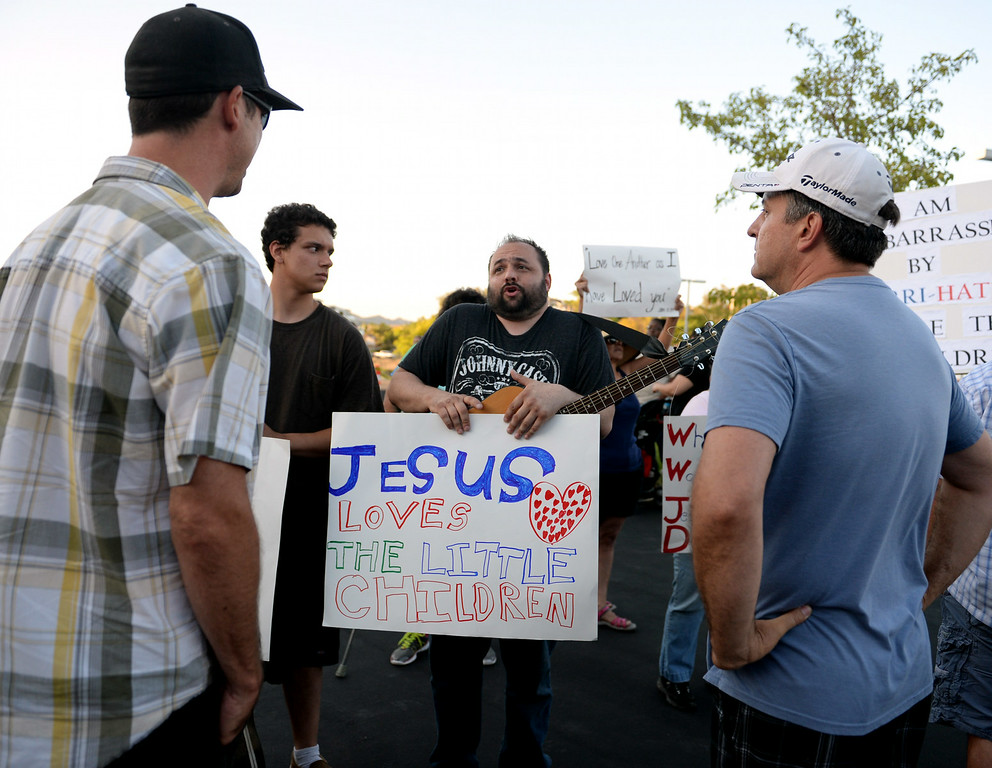 Description of . Joseph Aszterbaum, 39, center, of Hemet, and Kyler Aszterbaum, 16, left, discuss immigration issues outside a town hall meeting on Wednesday, July 2, 2014 at Murrieta Mesa High School in Murrieta, Ca. The meeting is being held in response to immigrants who were being processed through a Texas Border Patrol Station and delivered to the Murrieta Border Patrol Station on Tuesday, which created protests from both sides of the immigration issue. (Micah Escamilla/The Sun)
