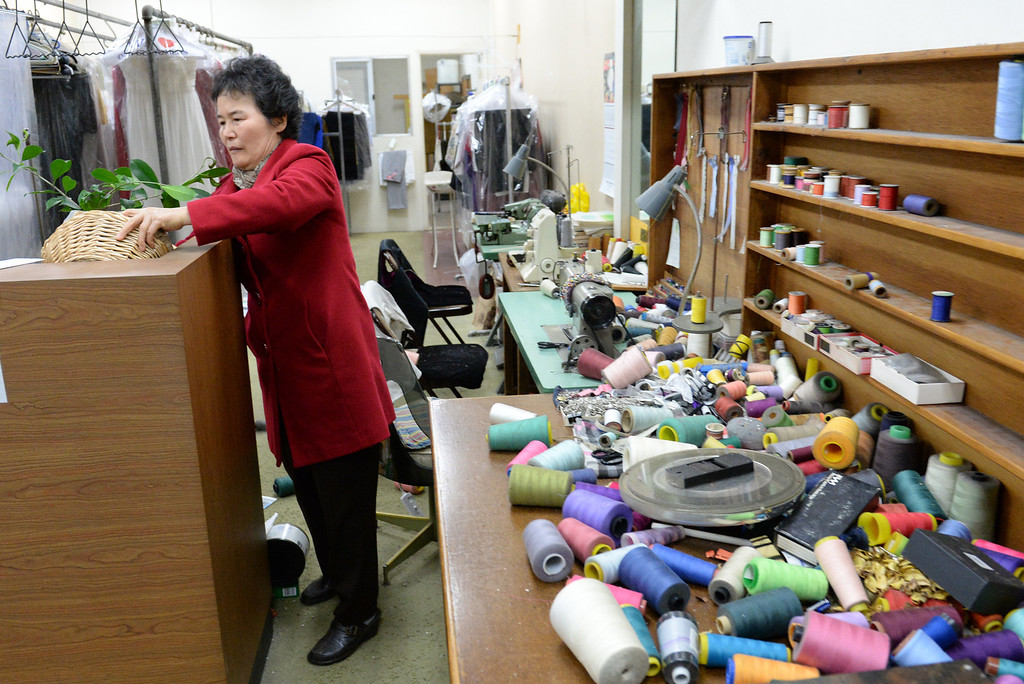Description of . Sherry Kim, owner of Towne Cleaners, looks over the damage after the 5.1 eartchquake at her shop in La Habra on Friday March 28, 2014. (Staff Photo by Keith Durflinger/Whittier Daily News)