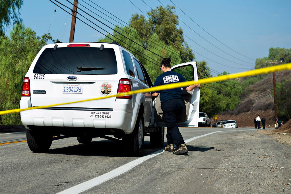 Description of . Los Angeles County coroner arrives at the scene where an unidentified burned body was found along the side of Covina Hills Road west of Via Verde Street in the unincorporated area of Covina on Tuesday morning, August 20, 2013. (SGVN/Staff photo by Watchara Phomicinda)