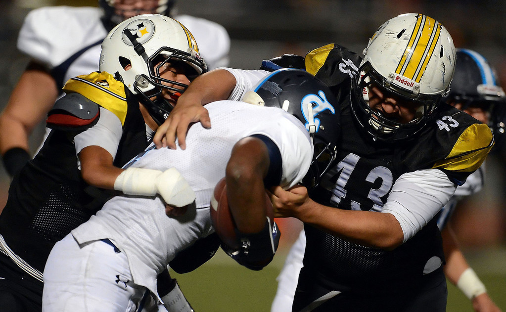 Description of . Bassett's Brandon Garfias, left, tackles Duarte's Sam Edwards, center, along with Andres Esparza (43) in the first half of a prep football game at Bassett High School in La Puente, Calif., on Friday, Nov. 1, 2013.    (Keith Birmingham Pasadena Star-News)