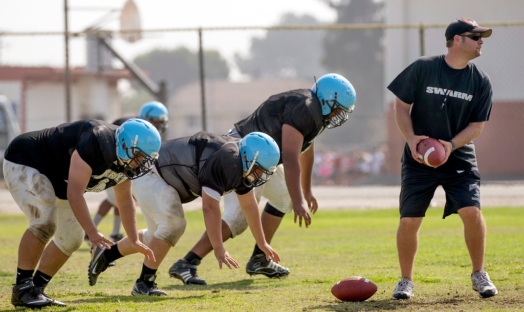 Description of . Arroyo High football offensive coordinator Chris McMillan leads a conditioning drill during preseason practice at the El Monte campus August 14, 2013.   (SGVN/Staff photo by Leo Jarzomb)