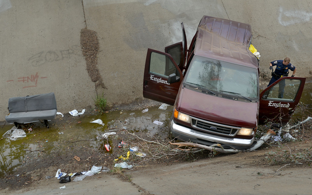 """Description of . One person died and nine others were injured when a van plunged down the side of the 10 Freeway, in Bloomington, Thursday April 17, 2014. According to the CHP, the driver of the van apparently lost control of the vehical after hitting the brakes while approaching traffic. """"As the van left the freeway lanes, it struck a tree and began to overturn and eventually landed in a drainage ditch,"""" said CHP Officer Leon Lopez. (Photo by Rick Sforza/The Sun)"""