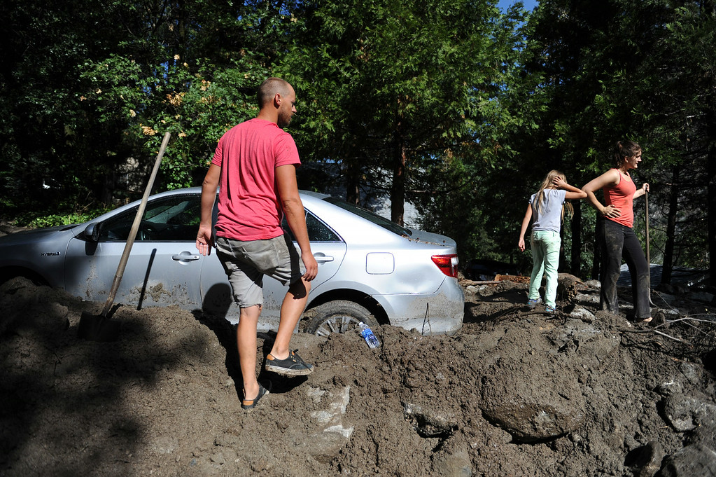 Description of . Neighbor Jacob Joff, left, helps dig out the car of Courtney Ehrlich, right, who was visiting from Redlands when the storm hit, on Monday, August 4, 2014 in Forest Falls, Ca. Sunday's flash flood closed parts of Valley of the Falls Drive was  re-opened late Monday morning. (Micah Escamilla/San Bernardino Sun)