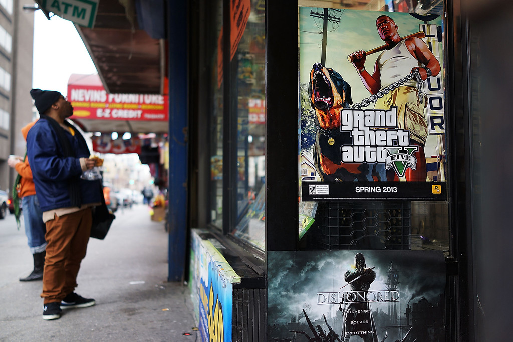Description of . NEW YORK, NY - JANUARY 11:  An advertisement for the new Grand Theft Auto is displayed outside of a gaming store on January 11, 2013 in New York City.  Following the shootings of children at a elementary school last month in Connecticut, numerous politicians and activists have begun to focus on violence in video games and films. US vice-president Joe Biden is meeting with games industry representatives today to discuss graphic violence, often with guns, in many of today's most popular video games.  The administration is also expected to address violence in the film industry as well.  (Photo by Spencer Platt/Getty Images)