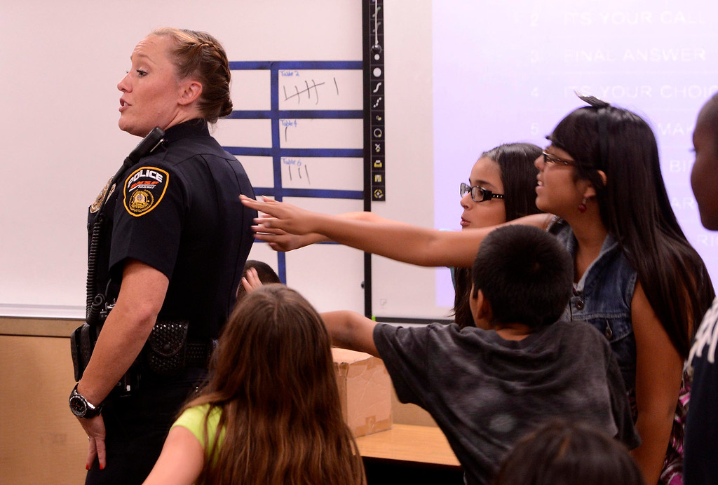 Description of . BNSF Railway Police Senior Special Agent Aimee Schmidt lets third graders touch her flak jacket during the final day of the 19th Annual Career Awareness Week at Lankershim Elementary School in Highland June 6, 2013.  GABRIEL LUIS ACOSTA/STAFF PHOTOGRAPHER.