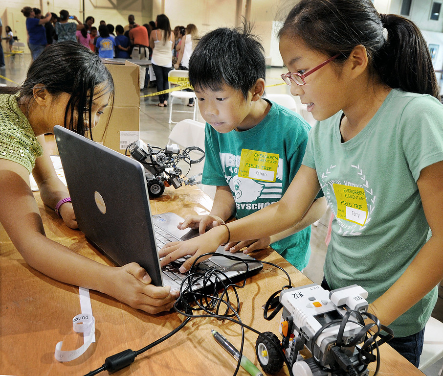 Description of . Karen Su, left, Ethan Wei, and Terry Kim of Evergreen Elementary in Walnut Valley programming their teams robots during competition. Cal Poly Pomona's Robotics Initiative invited 200 elementary and middle school students to a Robot Expo at LA Fairplex in Pomona Monday, May 20, 2013. (SGVN/Photo by Walt Mancini)