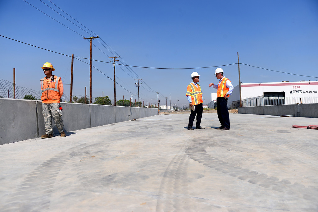 Description of . Ricky Choi, community relations project manager of ACE, and Mark Christoffels, right, CEO and chief engineer of ACE, walk over the newly built railroad bridge on the northern half of the grade separation at Baldwin Avenue and Gidley Street in El Monte Friday, May 16, 2014. The 2-year project, which closed Baldwin Avenue, is one of 22 underpasses from Los Angeles to Pomona that are done or expected to be completed by 2019. Baldwin Avenue is halfway complete. (Photo by Sarah Reingewirtz/Pasadena Star-News)