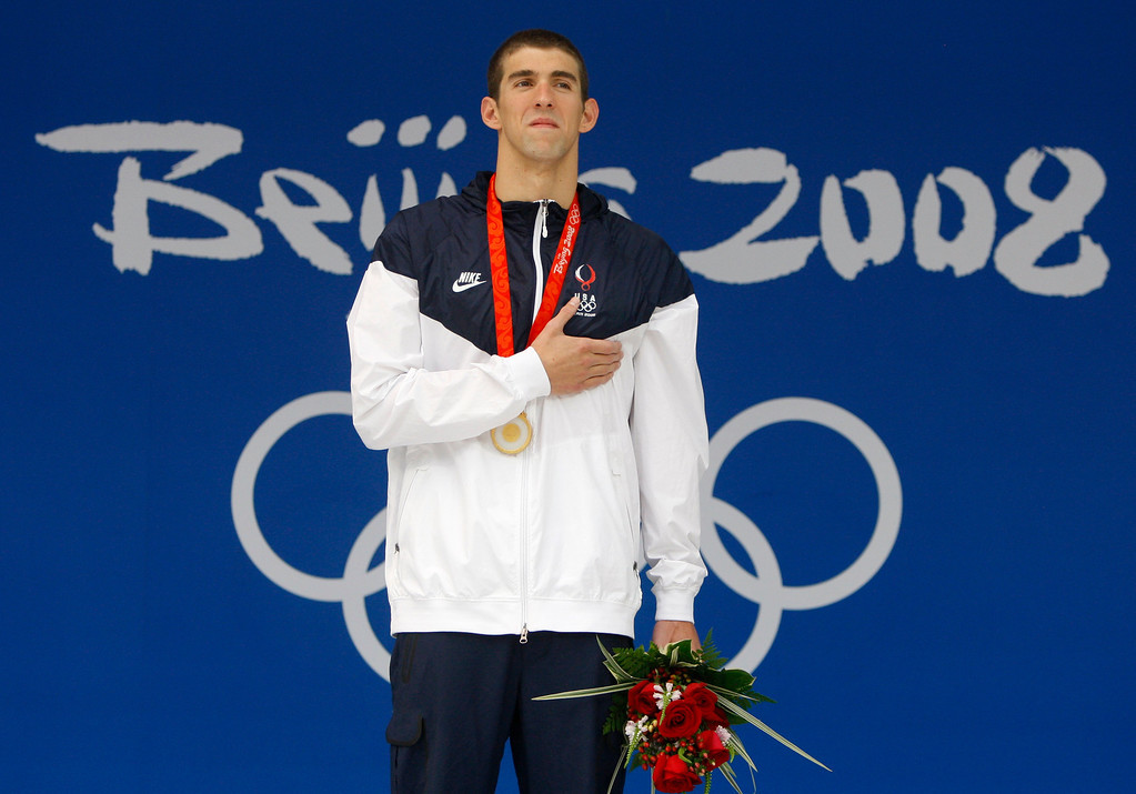 Description of . United States' Michael Phelps with his the gold medal during the presentation ceremony for the men's 100-meter butterfly final during the swimming competitions in the National Aquatics Center at the Beijing 2008 Olympics in Beijing, Saturday, Aug. 16, 2008.  (AP Photo/Mark Baker)