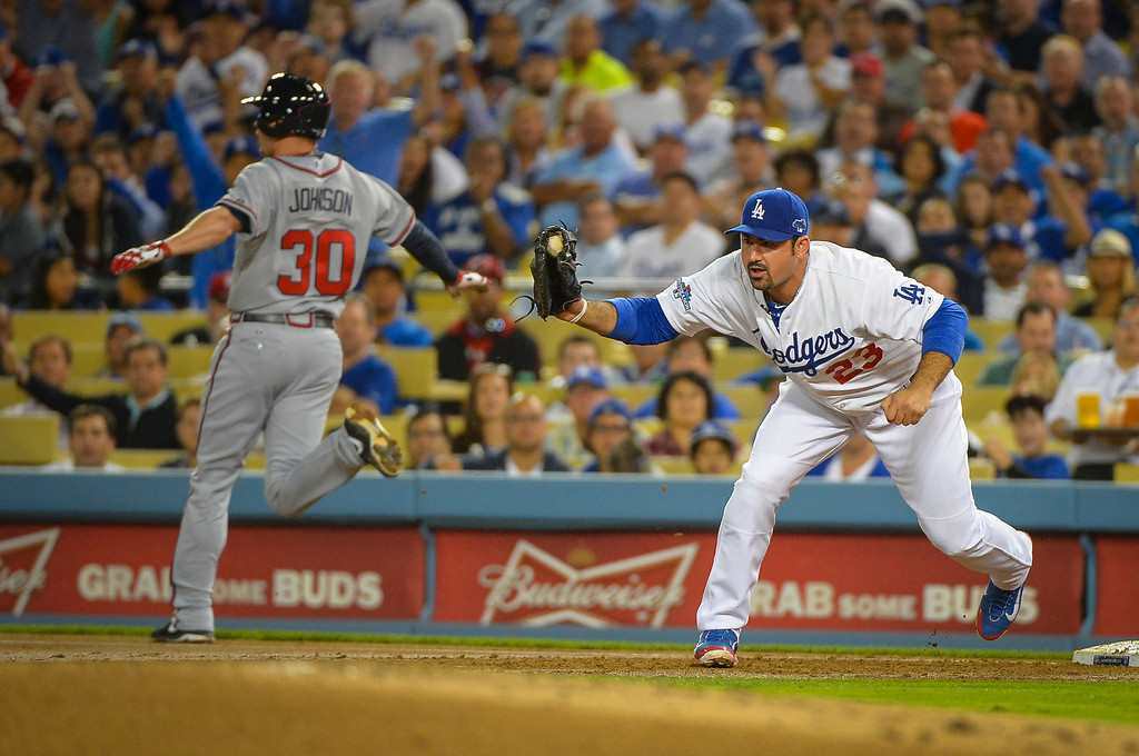 Description of . Dodger's Adrian Gonzalez gets Atlanta's Elliot Johnson out at first on a throw from Juan Uribe during game action Monday, October 7, 2013 ( Photo by Andy Holzman/Los Angeles Daily News )
