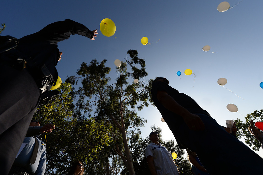 Description of . Friends and police officers pay tribute to Glendora Police Officer Louis Anthony Pompei at his memorial on Puente Street in San Dimas by releasing balloons with hand written messages Monday afternoon June 9, 2014. Pompei was killed in the line of duty at a near by market during a robbery attempt in June 1995. (Will Lester/Inland Valley Daily Bulletin)