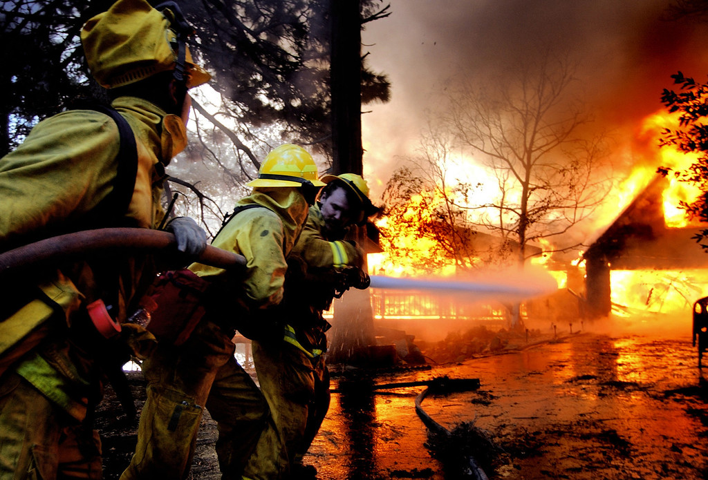 Description of . Ten years ago this month the arson caused Old Fire, fanned by Santa Ana winds burned thousands of acres, destroyed hundreds of homes and caused six deaths. The fire burned homes in San Bernardino, Highland, Cedar Glen, Crestline, Running Springs and Lake Arrowhead and forced the evacuation of thousand of residents. Fire fighters try to reach a house on fire near Crestline, on Sunday October 26, 2003 on the second day of the Old Fire. (Staff file photo/The Sun)