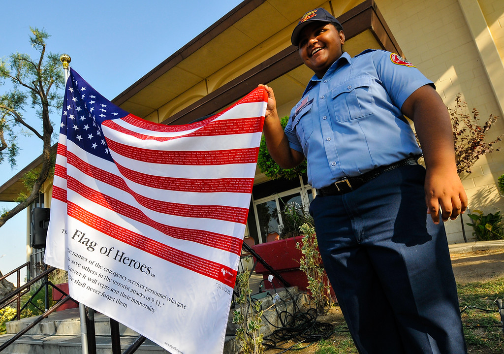 Description of . Cadet Rommie Crump (cq), 16, takes a picture with an American flag written with the names of first responders who gave their lives in the 9/11 terrorist attacks that was displayed during a 9/11 remembrance ceremony at the Public Safety Academy in San Bernardino on Wednesday, Sept. 11, 2013. (Photo by Rachel Luna / San Bernardino Sun)