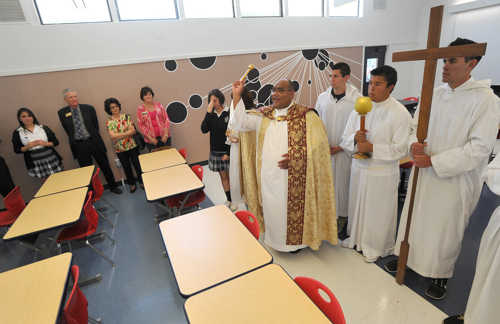 Description of . Father John-Paul Gonzalez blesses the classrooms as they celebrate their new $650,000 Science Center at St. Paul High School in Santa Fe Springs on Thursday May 2, 2013. The Science Program and Technology Infrastructure will enable the school to offer state-of-the-art science programs. (SGVN/Staff Photo by Keith Durflinger)