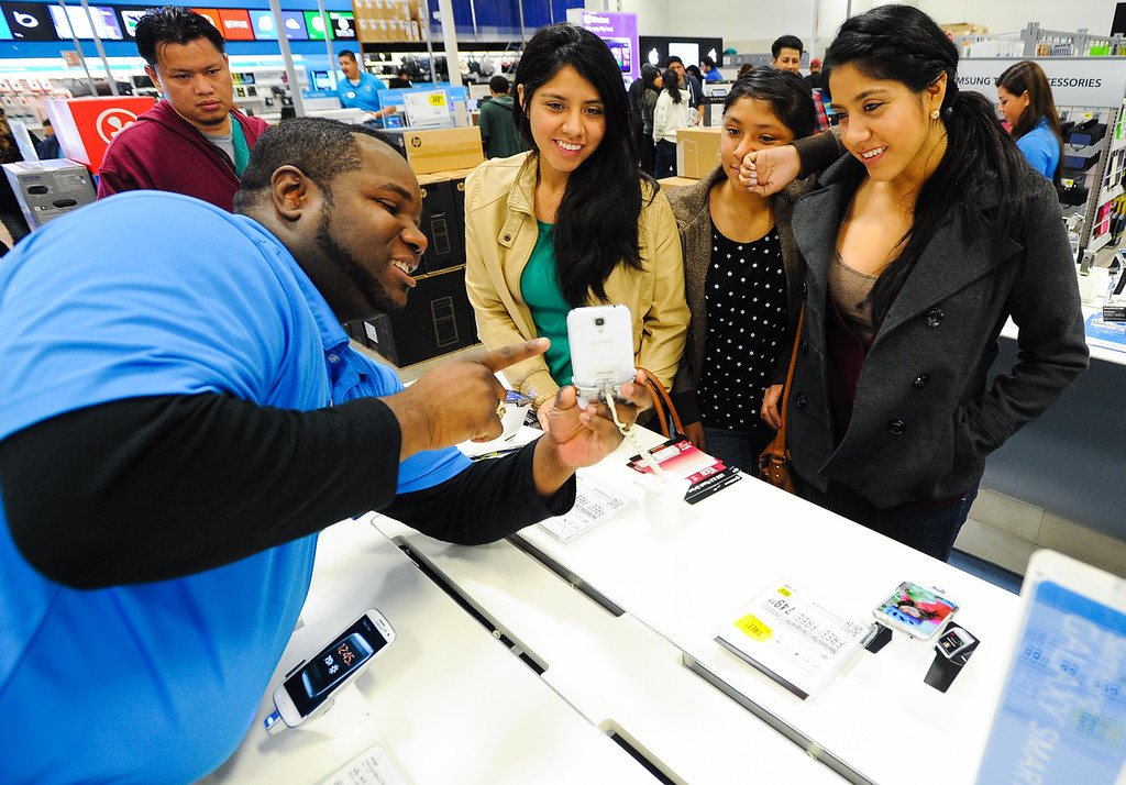 Description of . Best Buy employee Matt Nebedum, right, demos a smartphone for shoppers after the store opened its doors at 6 p.m. for early Black Friday sales on Thanksgiving in San Bernardino on Thursday, Nov. 28, 2013. Many retail stores pushed the boundary the Black Friday tradition this year with offering Black Friday deals on Thanksgiving day. (Photo by Rachel Luna / San Bernardino Sun)