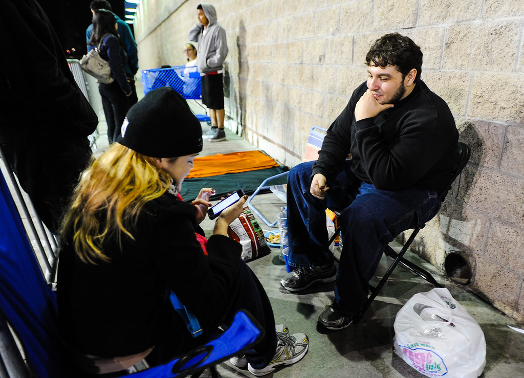 Description of . Highland resident Paul Andrade, right, and his friend Christina Carney, of Pomona, are the first shoppers to wait in line outside Best Buy for the store's