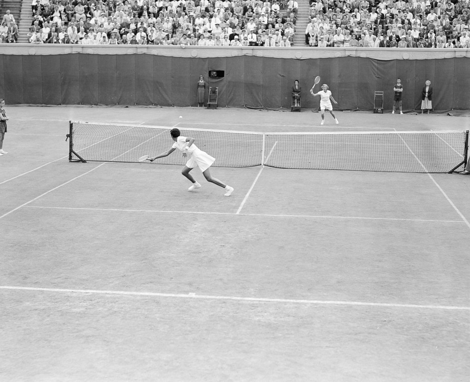 Description of . Wimbledon champion Althea Gibson of New York City shows the winning form that helped her capture the U.S. National Tennis Championships at Forest Hills, N.Y., Sept. 8, 1957, as she goes after a return by Louise Brough of Beverly Hills, far court.  (AP Photo/Harry Harris)