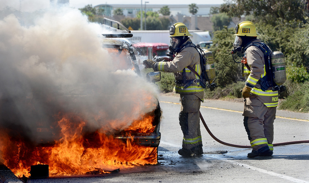 Description of . Ontario firefighters Danny Reza, left, and Tommy Pacheco get water on a vehicle fire on the Vineyard offramp Thursday May 2, 2013. Marco Perez of Riverside said he smelled gas coming from his truck and pulled over to the shoulder of the Vineyard Avenue offramp of the westbound 10. No one was injured and the cause of the fire is under investigation. (Rick Sforza/Inland Valley Daily Bulletin)