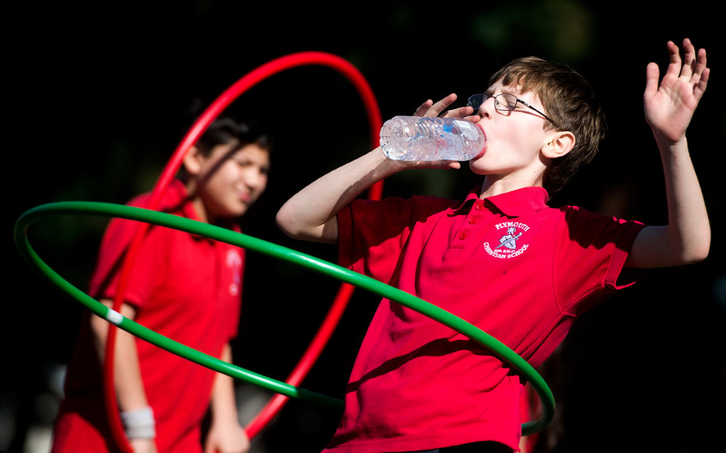 Description of . Ezera Vlad, 9, spins a hula-hoop while drinking water as the fourth grade class exercice at Plymouth Christian School in Whittier on Friday, Feb. 14, 2014. The school held the exercise event to promote good health. (Photo by Watchara Phomicinda/ Whittier Daily News)