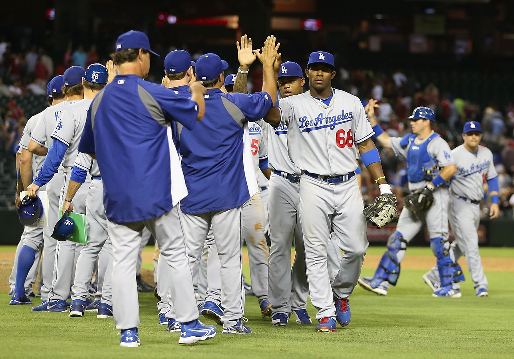 Description of . Yasiel Puig #66 of the Los Angeles Dodgers high fives teammates after defeating the Arizona Diamondbacks in the MLB game at Chase Field on July 8, 2013 in Phoenix, Arizona. The Dodgers defeated the Diamondbacks 6-1.  (Photo by Christian Petersen/Getty Images)