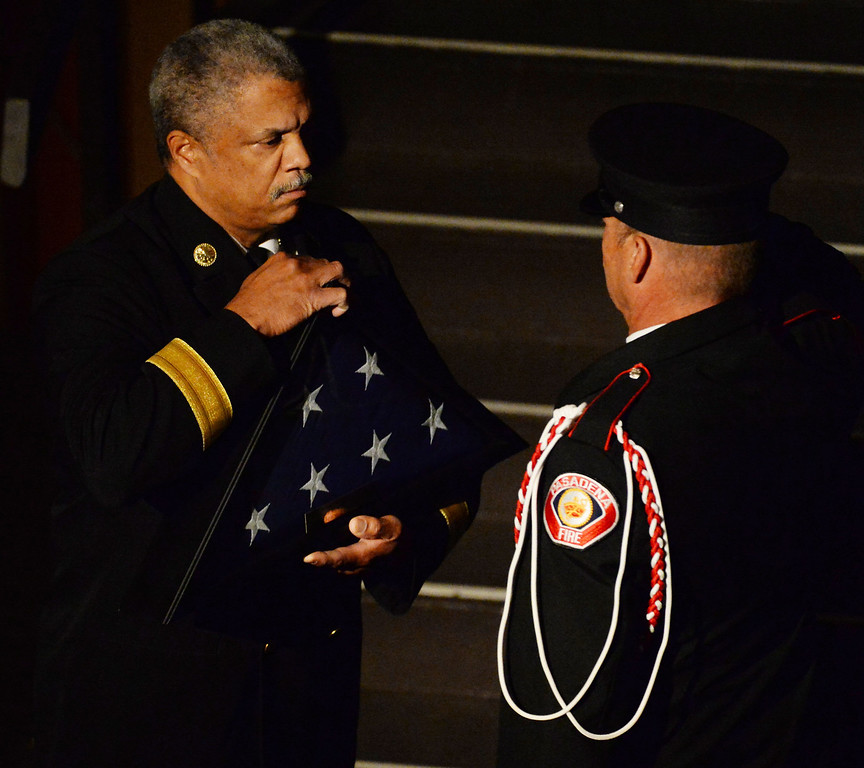 Description of . Pasadena Fire Chief, Calvin E. Wells, left, prepares to present the flag to the Tennant family during a celebration of life service for former Pasadena Fire dept. Capt. and California State fire marshall, John Tennant at the Pasadena Civic Auditorium in Pasadena, Calif., on Wednesday, Feb. 5, 2014. (Keith Birmingham Pasadena Star-News)