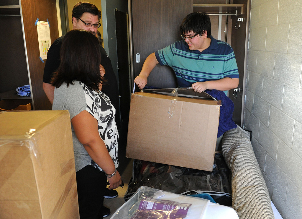 Description of . (John Valenzuela/Staff Photographer) Freshman student Jacob Kern of Highlands, unpacks in his new dorm room with his parents Renee and Blaine by his side, Wednesday moring during move-in day at the University of Redlands, August 28, 2013.
