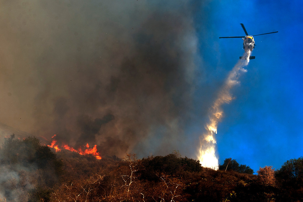 Description of . LA County Fire helicopter makes a water drop near Big Dalton in Glendora, Calif. on Thursday, Jan. 16, 2014. (Photo by Watchara Phomicinda/ San Gabriel Valley Tribune)