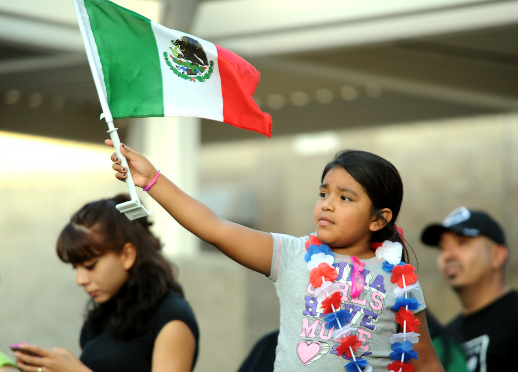 Description of . Emily De Los Angeles, 6, of Boyle Heights, waves a mexican flag during a town hall meeting on Wednesday, July 2, 2014 at Murrieta Mesa High School in Murrieta, Ca. The meeting is being held in response to immigrants who were being processed through a Texas Border Patrol Station and delivered to the Murrieta Border Patrol Station on Tuesday, which created protests from both sides of the immigration issue. (Micah Escamilla/The Sun)