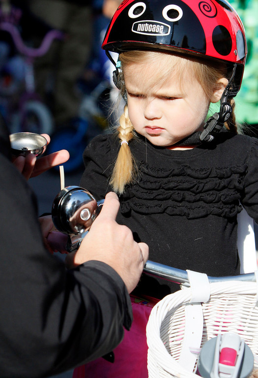 Description of . Chloe Mead, 3, of Redlands, watches her father, Chris, fixes her bell prior to the public race portion of the Redlands Bicycle Classic on Saturday, April 5, 2014 in Redlands, Ca. (Photo by Micah Escamilla for the Redlands Daily Facts)