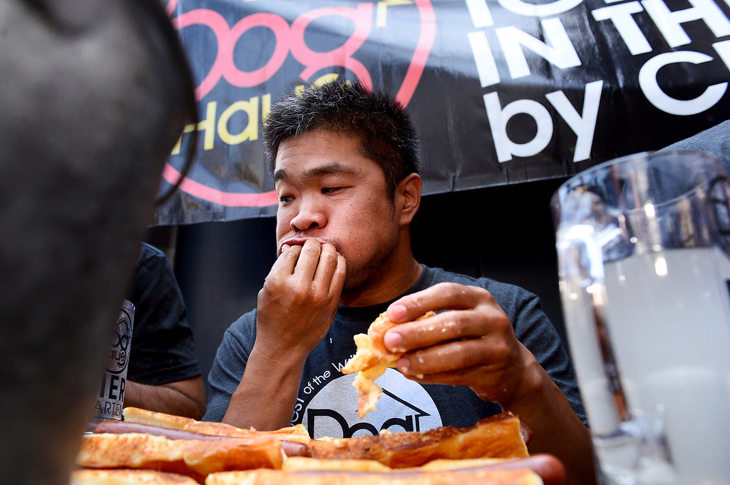 Description of . Jimmy Lin, of Anaheim, wins the First Annual Hot Dog Eating Competition at Dog Haus Biergarten in Old Pasadena Saturday, July 6, 2013. Lin ate 11 dogs, 3 during a tiebreaker.  (SGVN/Staff Photo by Sarah Reingewirtz)