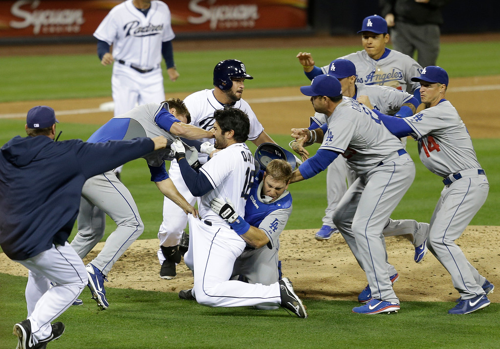 Description of . San Diego Padres' Carlos Quentin charges into Los Angeles Dodgers  pitcher Zack Greinke after being hit by a pitch in the sixth inning of baseball game in San Diego, Thursday, April 11, 2013. Greinke suffered a broken left collarbone. Dodgers won 3-2.   (AP Photo/Lenny Ignelzi)