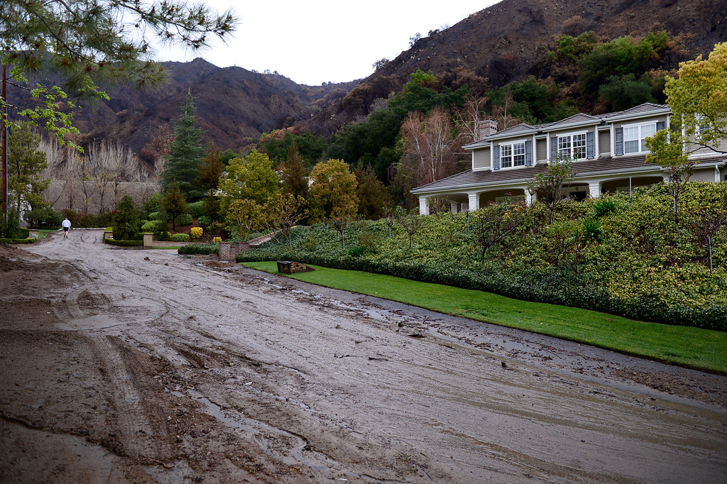 Description of . A resident in the Easley Estates in Glendora walks up his muddy driveway Saturday morning, March 1, 2014. The homes sit below the Colby Fire burn area.  (Photo by Sarah Reingewirtz/Pasadena Star-News)