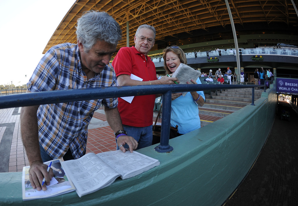 Description of . Mark Batlin, left, looks over the racing program as Wright Batlin, center, and Kathy Parnello of Northern California look on prior to the Breeders' Cup at Santa Anita Park in Arcadia, Calif., on Saturday, Nov. 2, 2013. 