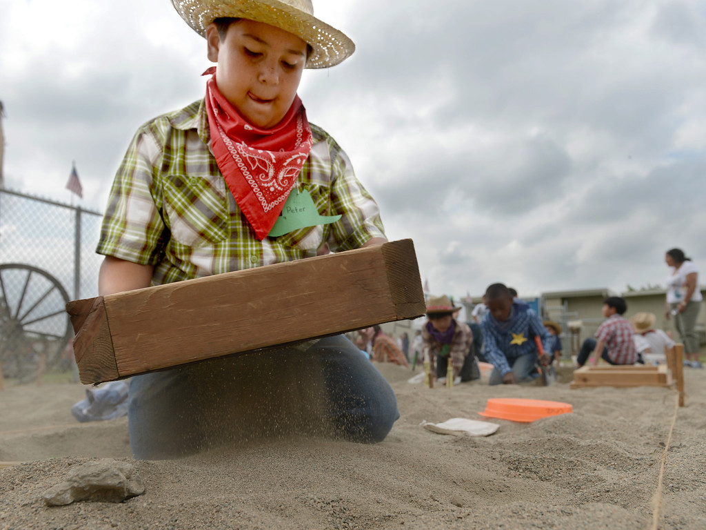 Description of . Peter Cruz, 10, shifts through dirt as he pans for gold at the annual Gold Rush Day at Sierra Vista Elementary School in Upland May 17, 2013. About 60 students paned for gold while learned all about the Gold Rush at the school.  (Thomas R. Cordova/Staff Photographer)