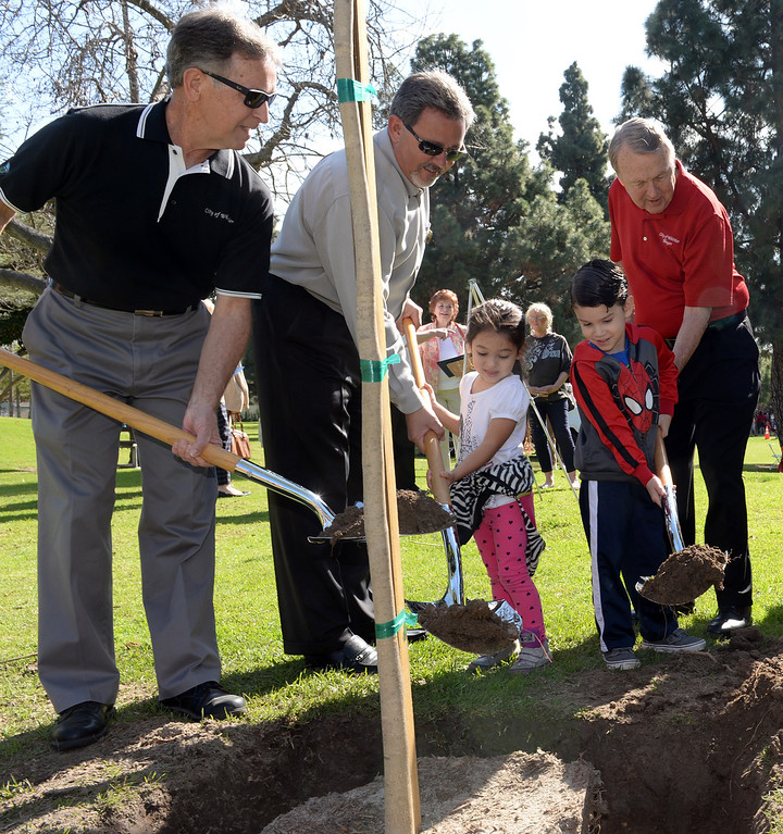Description of . City council members Owen Newcomer, left, Fernando Dutra, center and Mayor Bob Henderson help school children, from left, Sofia Altimirano, Justin Alvarado plant a tree during the Annual Arbor Day celebration at Michigan Park in Whittier on Thursday March 13, 2014. Children were able to help plant trees, see demonstrations by city workers and see information booths from area conservation groups. (Staff Photo by Keith Durflinger/Whittier Daily News)