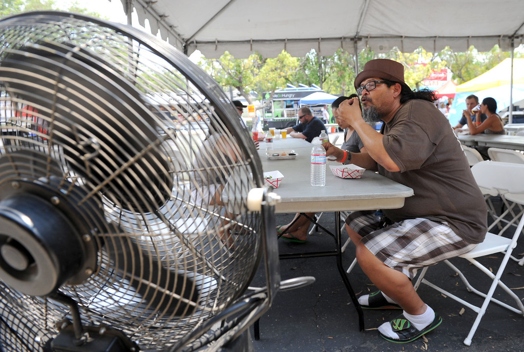 Description of . (John Valenzuela/Staff Photographer) Mark Cruz of San Bernardino cools-off in front of a Fan, as he eats his food during the second annual Food Truck and Brewfest in Redlands Saturday, June 29, 2013.